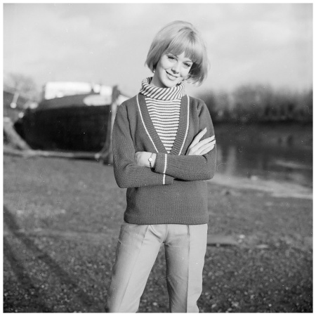 A young woman with folded arms models a striped polo neck jersey with a deep v-neck jumper. 1965 (Photo by Chaloner Woods:Getty Images)