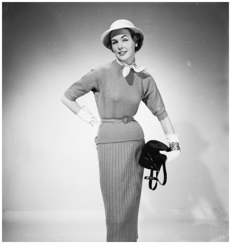 Barbara Goalen wears a knitted jumper suit , tightly belted and worn with gauntlet gloves and a scarf tied at the neck. The outfit is completed with a small brimmed hat with a round crown. 1953 (Photo by Chaloner Woods:Getty Images)