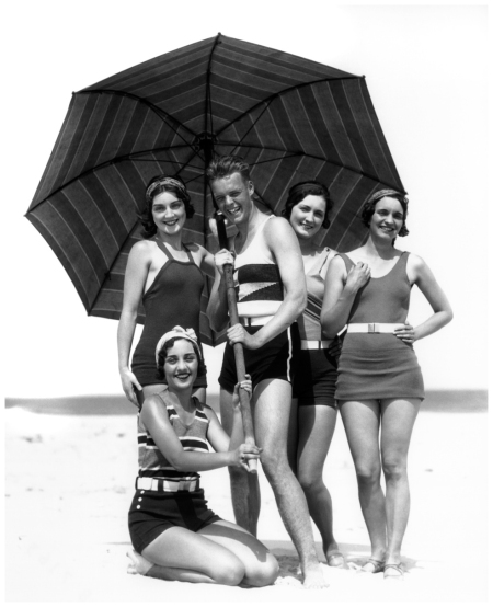 Four Women And One Man Under Beach Umbrella In Bathing Suits; Four Standing, One Woman Kneeling On Beach, Outside. All Are Smiling.. (Photo by H. Armstrong Roberts Getty Images)