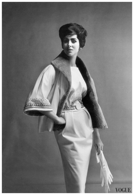 Maggi Eckardt is wearing oyster-white satin gown embroidered with bronze and grey beads, the jacket lined and collared in beaver by Norman Hartnell, photo by Vernier, Vogue UK, September 1959
