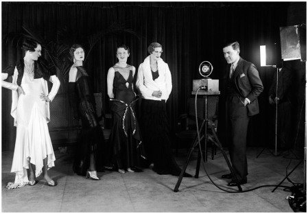 Norman Hartnell 1930, the famous young English dress designer, is taking to Paris some of his latest British fashions to compete with French designers. In the picture Mr Hartnell is describing his models while being filmed for Movitone News