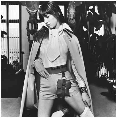 Jane Birkin by Patrick Lichfield. See Vogue, March 15, 1971 FAIRCHILD ARCHIVE Jane Birkin, French singer:actress, wearing white stripped shirt with tie; cotton cape and short shorts by Luba, belt with satchel bag, and watch with wide band by Sheffield