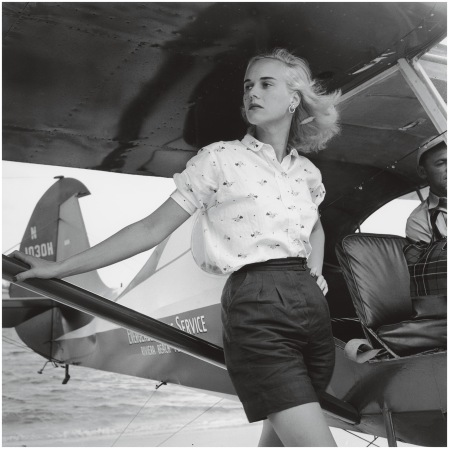 Patsy Pulitzer leaning against a seaplane belonging to the Everglades Flying Service, at Palm Beach, Florida, 1955 Photo Slim Aarons