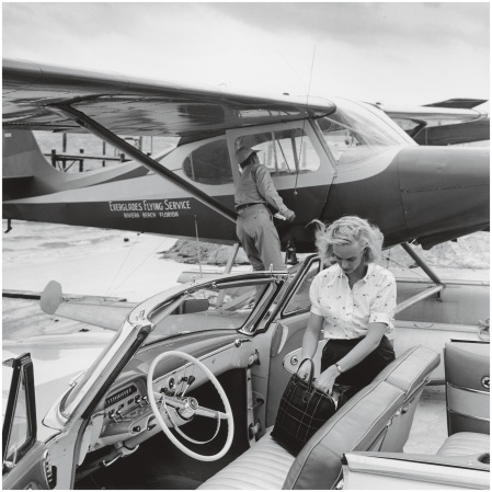 Patsy Pulitzer rummaging in her bag on the seat of an open car Palm Beach, Florida, 1955 Photo Slim Aarons