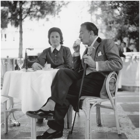 Salvador Dali enjoying a cup of coffee with his wife Gala on a terrace at the Ritz Hotel, Madrid.