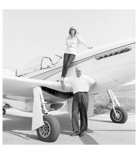 Woman standing on wing of small airplane, man standing next to airplane