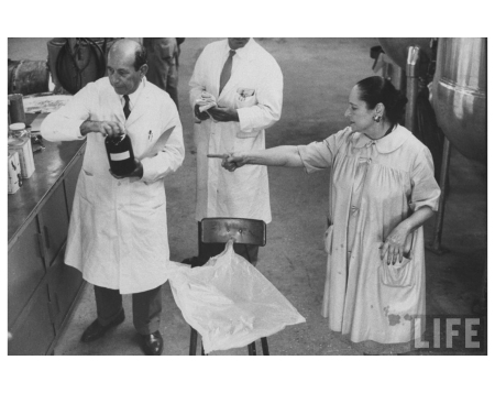 Helena Rubenstein (R), wearing a smock with chemists in perfume blending lab