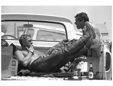 Steve McQueen takes a lunch break during a motorcycle race with Bud Ekins, his friend and stuntman for The Great Escape, 1963.