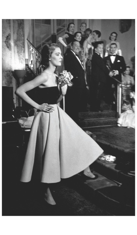 A Model waiting to go on at fashion show; in background, designer Charles James is standing on steps with models wearing dresses from his collection 1950 Photo Eliot Elisofon