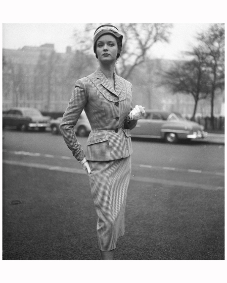 A woman modelling a tailored suit by Simon Massey, with white gloves and a hat. 1953 Chaloner Woods