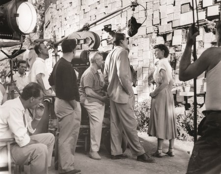 "Hepburn chats with Peck, director William Wyler, and the crew on location for Roman Holiday at the ""Wall of Wishes,"" in Rome"